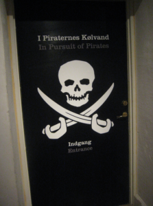 "Some museums produce bilingual or multilingual exhibitions. But what do we know about international museum visitors? Photo from the entrance to the bilingual exhibition ""In Pursuit of Pirates - The Danish Navy vs. Pirates in Five Centuries"" or in Danish: ""I piraternes kølvand – flådens kamp med pirater i 500 år"" at Orlogsmuseet, Copenhagen, 2012. Photo: Jonas Abkjær Andersen"